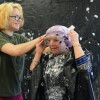 Junior Chloe Neighbor helps Mrs. Fishman put on goggles before she is pied. Photo by Annika Sink