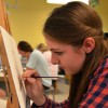 Junior Lindsey Filger is painting a new project, inspired by a photo of a bridge surrounded by greenery. The students first sketch out the landscape, then paint in the canvas. Photo by Annie Lomshek.