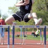 Freshman Frank Schudy jumps over the hurdle and finishes the race. Photo by Morgan Browning