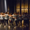 The varsity team forms a huddle onstage before the curtains open for their section of the MANcer Dancer performance. Photo by James Wooldridge