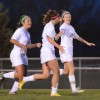 Josie Clough and Addie Griffith give their teammate Jessica Parker high fives for scoring a goal. Photo by Annika Sink