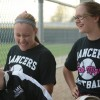 """Sophomores Emma Chalk and Makenzie Fankhauser laugh in the dugout with senior Emily Budzowski. """"We were laughing about the game and having a good time,"""" Budzowski said. Photo by Kylie Rellihan"""