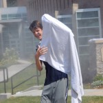 Freshman Davis Vaughn uses a towel to shield himself from the spray of the power hose.  Photo by Tess Iler