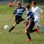 Freshman Charlie Colby kicks the ball away from opponent. Photo by Abby Walker