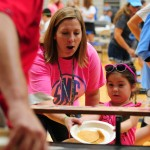 Lancer Dancer coach Alexis Close, also known as Bubba, helps her daughter catch pancakes. Photo by Katie Lamar