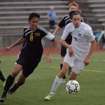 Junior Clayton Phillips kicks the ball away from two West defenders. Photo by Morgan Browning