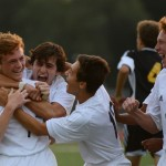 Sophomore Tommy Nelson thrills his teammates after he scores the first goal of their season. Photo by Annie Lomshek.