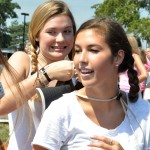 Sophomore Daisy Bolin braids Sophomore Sophie Barreca's hair before the parade starts. Photo by Ellie Thoma