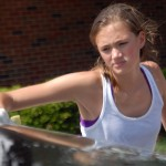 Freshman Maeve McKinney washes the roof of car with a sponge.  Photo by Tess Iler