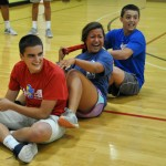 Sophomore Reser Hall, sophomore Charlie Moreland, and senior Addie Rose Griffith laugh while playing games in the gym.