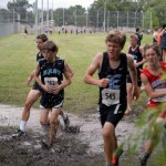A group of C-Team boys run through a deep mud puddle during the first half of the race.  Photo by Tess Iler