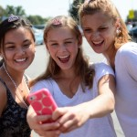 "Juniors Devon Dietrick, Carolyn Kinney and Emma Cannova take a picture of themselves before the parade begins. Cross Country's theme was ""Rolling out the red carpet for the Lancers"". Photo by Morgan Browning"