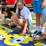 Freshman Lucy Kendall, Annabelle Cook, and Liddy Stallard paint minion posters for Lancer Day. Photo by Diana Percy