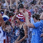 The USA themed student section throws confetti in celebration of a touchdown. Photo by Diana Percy