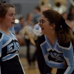 Varsity cheerleaders, Tyler Lockton and Lily Horton, laughing at each other before their first cheer. Photo by Ava Simonsen