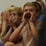 Junior William Larson and Senior Davis Finke cheer for the Varsity girls after they get a kill. Photo by Kaitlyn Stratman
