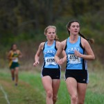 Sophomore Madeline Hoblik and junior Libby Wilson push to maintain position in the middle of the pack. Photo by Joseph Cline