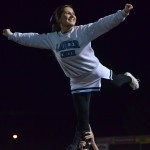 Senior Halle Connelly stunts alongside other varsity cheerleaders. Photo by Abby Blake