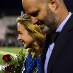 Senior and homecoming queen Chloe Kerwin smiles while walking down the track with her dad. Photo by Diana Percy