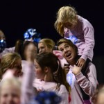 Sophomore Ava Renko hoists a little Lancer onto her shoulders after a touchdown. Photo by Diana Percy