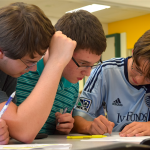 Sophomore Zach Krause works solves the problem while his team checks his work. Photo by Anna Kanaley