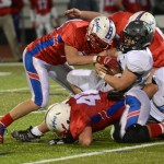 Senior Wyatt Edmisten is tackled by Olathe North players during one of the first plays in the third quarter. Photo by Haley Bell
