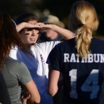 Junior Kalin Lamus blocks the sun from her eyes while listening teammates to the varsity football players' feedback. Photo by Kaitlyn Stratman