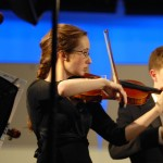 Senior Ellie Stewart-Jones and junior Ben Robinson play violin during the chamber orchestra performance.  Photo by Tess Iler