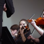 Senior Bethany Snyder watches the conductor while playing her viola.  Photo by Tess Iler