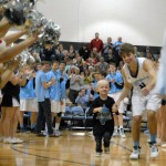 Senior Alex Glazer leads Tyler, a cancer patient, out after he is introduced during the team introductions.  Photo by Tess Iler