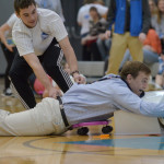 """During the life-sized """"Hungry Hippo"""" game, junior Grayson Rapp pulls teammate, junior Eli McDonald across the floor in a fight to win. Photo by Abby Blake"""