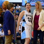 Senior Sara Nestler laughs with her coach and mother after being announced on girls' basketball senior night. Photo by Diana Percy