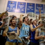 The student section tosses newspaper shreddings in the air after the varsity lineup was announced. Photo by Ellie Thoma