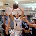 Junior and Varsity basketball player Trevor Thompson  forces through the defense to take a shot. Photo by Ellie Thoma