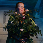 Junior Haley Lynch, as Joy, hides behind a bush after Prince Charming and Cinderella talk with each other. Photo by Morgan Browning