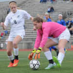 As the Olathe South goalies bends to pick up the ball, junior Lilly Flint follows through on the play. Photo by Haley Bell