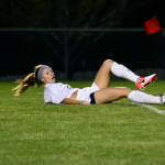 Junior Josie Clough slides onto the ground after kicking the ball to a teammate. Photo by Diana Percy