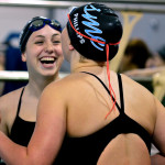 Freshman Emma Broaddus laughs with her freshman teammate Hannah Phillips before their heat. Photo by Diana Percy