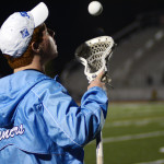 Team manager, Junior Taylor Norden, tosses a ball while watching the game from the sideline. Photo by Kaitlyn Stratman