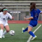 Freshman Emily Cooper prepares to kick the ball down the field before her opponent reaches it. Photo by Kaitlyn Stratman