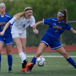 Junior Lilly Flint kicks the ball away as an Olathe-South attempts to stop her. Photo by Kaitlyn Stratman