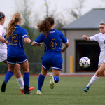 Junior Ellie Booton prepares to clear the ball from the goal and her opponents. Photo by Kaitlyn Stratman
