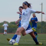 Freshman Izzy Rapp beats her opponent to the ball and kicks it to a teammate down the field. Photo by Kaitlyn Stratman