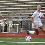 Senior Elisabeth Shook begins to turn to pass the ball as she approaches the corner of the field. Photo by Kaitlyn Stratman