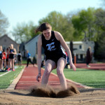 Sophomore Laura Adams lands her long jump.  Photo by Tess Iler