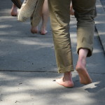 Coalition sponsor David Muhammad carries his Toms as he walks barefoot along Mission Road. Photo by Jemima Swindells
