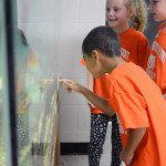 One of the kids points at the fish in the tank while the others laugh. Photo by Kaitlyn Stratman