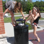 Sophomores Loren Davis and Harper Mundy attempt to stuff the Toms' Day sign into a trashcan outside of Chipotle after the walk. Photo by Anna Kanaley