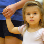 English teacher Mrs. Feinberg's daughter Eva watches the Lancer Dancers perform. Photo by Caroline Mills