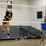 Senior Emma Henderson spikes the ball over the net while Coach Alex watches. Photo by Diana Percy